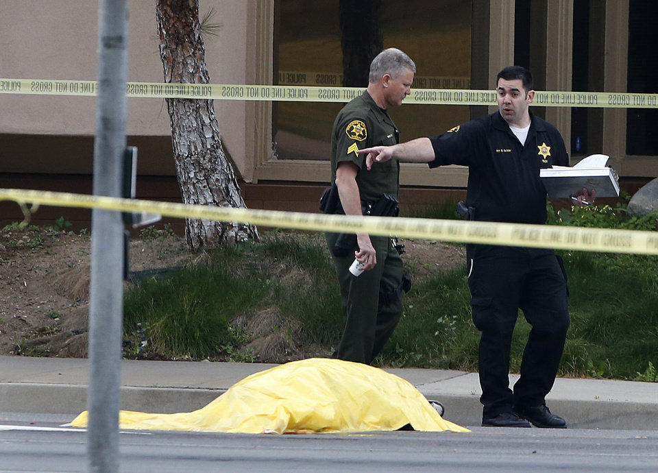 Investigators walk past a tarp covered body in Orange, Calif., Tuesday, Feb. 19, 2013. Police say a chaotic 25-minute shooting spree through Orange County left a trail of dead and injured victims before the shooter killed himself. Orange County sheriff\'s spokesman Jim Amormino say there are at least six crime scenes with three people, including the suspected gunman, dead and several others wounded. Tustin police Supervisor Dave Kanoti said the shootings started with an apparent carjacking just after 5 a.m. Tuesday in an unincorporated Ladera Ranch area of Orange County. (AP Photo/Jae C. Hong)