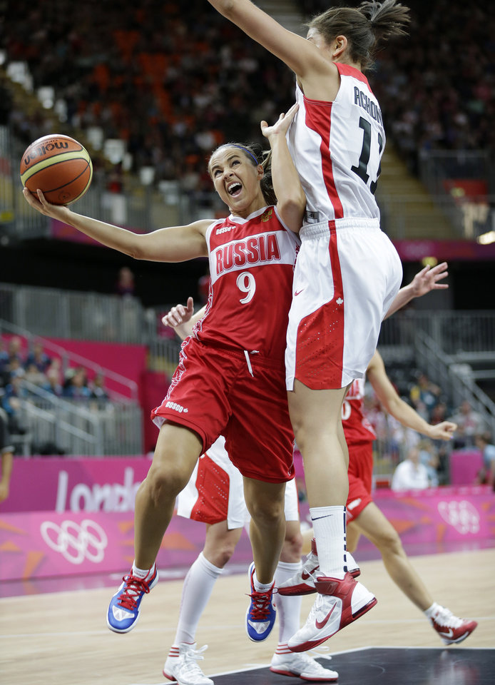 Photo - Russia's Becky Hammon (9) is defended by Canada's Natalie Achonwa, right, during the first half of a preliminary women's basketball game at the 2012 Summer Olympics, Saturday, July 28, 2012, in London. (AP Photo/Eric Gay)