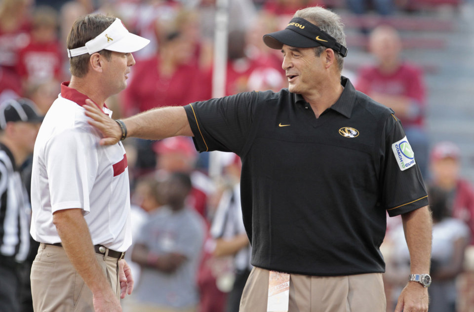 Photo - OU coache Bob Stoops (left) and Missouri's Gary Pinkel greet before their game Saturday in Norman. OU won 38-28.Photo by Steve Sisney, The Oklahoman