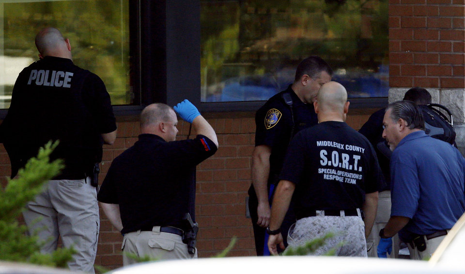 Photo -   Officials investigate the scene of a shooting at a Pathmark grocery store in Old Bridge, N.J., Friday, Aug. 31, 2012. At least three people have died in the shooting. A law enforcement official briefed on the shooting says the person believed to be the shooter is among the dead. (AP Photo/Julio Cortez)