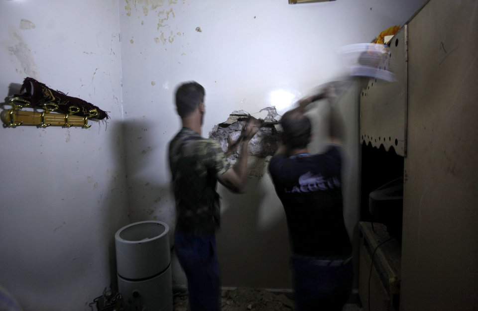 Photo -   Two Syrian men strike a wall to make a hole during a search for survivors in after it was hit by an airstrike in Aleppo, Syria, Friday, Aug. 17, 2012. Rebel footholds in Aleppo have been the target of weeks of Syrian shelling and air attacks as part of wider offensives by President Bashar Assad's regime. Rebels have been driven from some areas, but the report of clashes near the airport suggests the battles could be shifting to new fronts. (AP Photo/ Khalil Hamra)