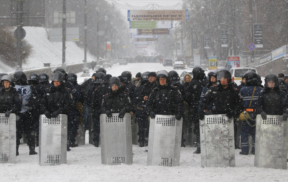 Photo - Ukrainian riot police block Pro-European Union activists gathered on the Independence Square in Kiev, Ukraine, Monday, Dec. 9, 2013. The policemen, wearing helmets and holding shields, formed a chain across Kiev's main street outside the city building. Organizers called on protesters to vacate the city hall and the other building which the opposition had used as its headquarters. (AP Photo/Sergei Grits)