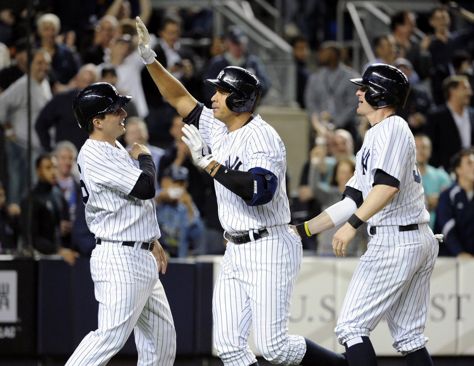 Photo - New York Yankees' Alex Rodriguez, center, celebrates with J.R. Murphy, left, and Brendan Ryan after Rodriguez hit a grand slam during the seventh inning of an interleague baseball game against the San Francisco Giants, Friday, Sept. 20, 2013, at Yankee Stadium in New York. (AP Photo/Bill Kostroun)