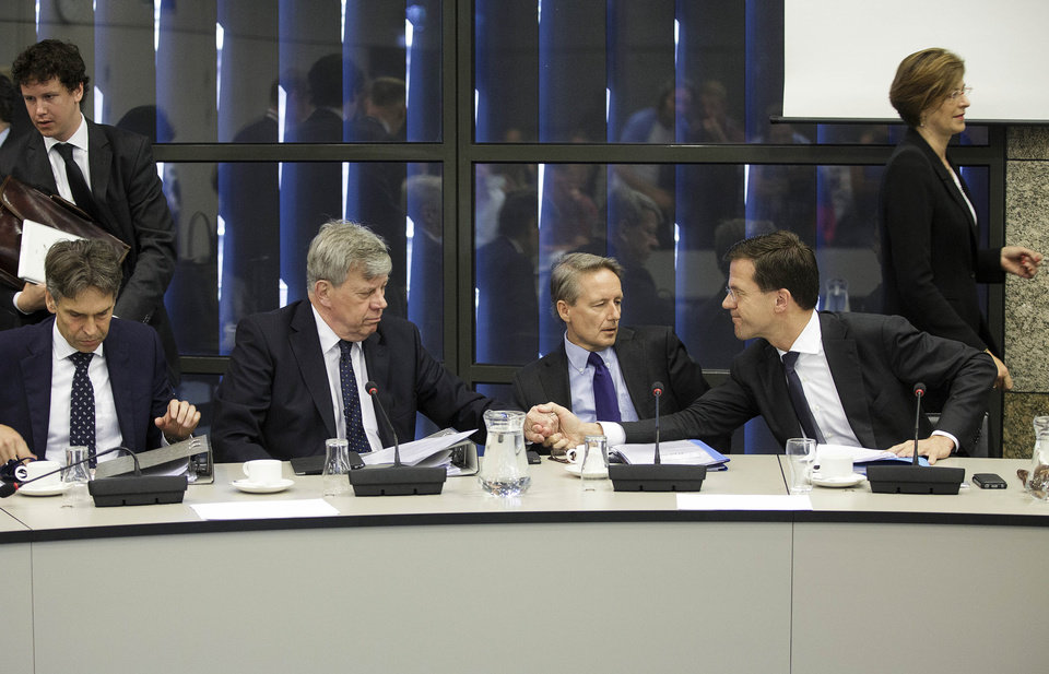 Photo - Dutch Prime Minister Mark Rutte, right, shakes hands with Dutch Justice Minister Ivo Opstelten, second left, at the start of a meeting in The Hague, Netherlands, Monday, July 21, 2014. Rutte briefed lawmakers about his government's response to Thursday's downing of Malaysia Airlines Flight 17 that claimed 193 Dutch lives. Rutte says he has made it 'crystal clear' to Russian President Vladimir Putin that he must use his influence with rebels to ensure unhinderd access to the crash scene for international investigators. (AP Photo/Phil Nijhuis)