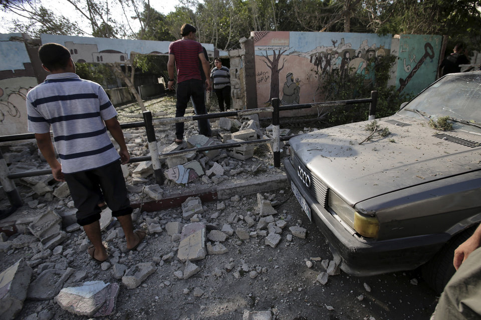 Photo - Palestinians look at the destroyed wall of Shifa hospital after an Israeli air strike on it, in Gaza, in the northern Gaza Strip, Monday, July 28, 2014. Israel's Prime Minister Benjamin Netanyahu said in a televised speech Monday that Israelis must be