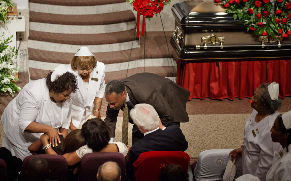 Photo - Donna Kelly Pratte, the mother of Kris Kross rapper Chris Kelly, seated second from left, is consoled during the funeral service for her son, Thursday, May 9, 2013, in Atlanta. The 34-year-old Kelly was found dead May 1 of a suspected drug overdose. Kriss Kross, the rap duo of Kelly and Chris Smith, was introduced to the music world in 1992 by music producer and rapper Jermaine Dupri after he discovered the pair at a mall in southwest Atlanta. (AP Photo/David Goldman)