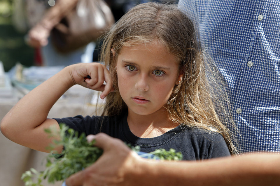Photo - Julia Gries, 8, of Norman, examines the pupa stage of a monarch butterfly's development at the Monarch Migration and Butterfly Festival Saturday at Cole. PHOTO BY STEVE SISNEY, THE OKLAHOMAN  STEVE SISNEY