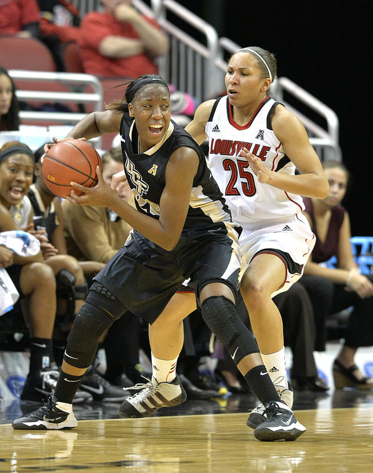 Photo - Central Florida's Sara Djassi, left, looks for help from the trapping defense of Louisville's Tia Gibbs during the second half of an NCAA college basketball game on Wednesday, Jan. 15, 2014, in Louisville, Ky. Djassi led all scorers with 28 points in her team's 75-56 loss. (AP Photo/Timothy D. Easley)