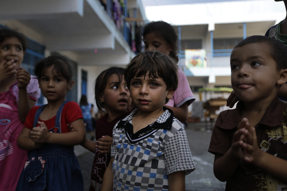 Photo - Displaced Palestinian Ahmed Al Attar, center, participates in a play session with other children, at a U.N. school where they had sought refuge along with their families during the war, in Gaza City, Gaza Strip, Thursday, Aug. 7, 2014. Taking advantage of the continuing ceasefire, volunteers from the local non-profit NGO 'Tomooh' (Ambition), arranged a special play session for children to try and lessen the stress they've been enduring after the weeks of conflict. In the playground the children got a chance to sing and play group games under the caring eye of volunteers. They hope that their efforts will lessen the damage of the traumatic recent weeks events, or at least help them forget for a short while. (AP Photo/Lefteris Pitarakis)