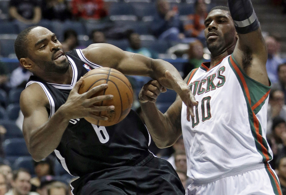 Photo - Brooklyn Nets' Alan Anderson is fouled as he tries to drive past Milwaukee Bucks' O.J. Mayo during the first half of an NBA basketball game Saturday, Dec. 7, 2013, in Milwaukee. (AP Photo/Morry Gash)