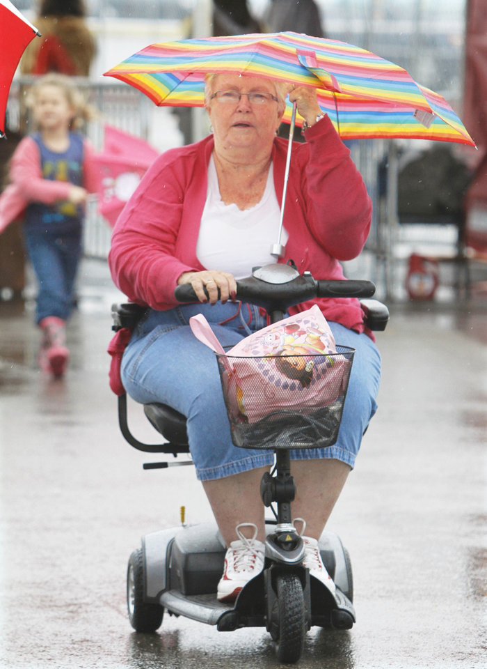 Betty Beavers uses her umbrella during opening day of the Oklahoma State Fair at State Fair Park in Oklahoma City, Thursday  September  13, 2012. Photo By Steve Gooch, The Oklahoman