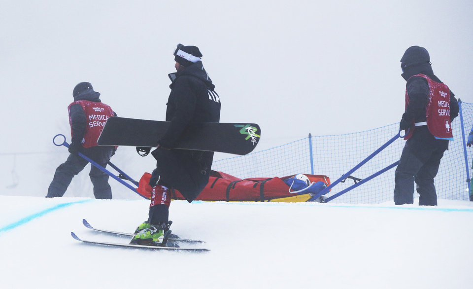 Photo - Italy's Omar Visintin is carried off the course in a stretcher after crashing in the second semifinal of the men's snowboard cross at the Rosa Khutor Extreme Park, at the 2014 Winter Olympics, Tuesday, Feb. 18, 2014, in Krasnaya Polyana, Russia.(AP Photo/Sergei Grits)