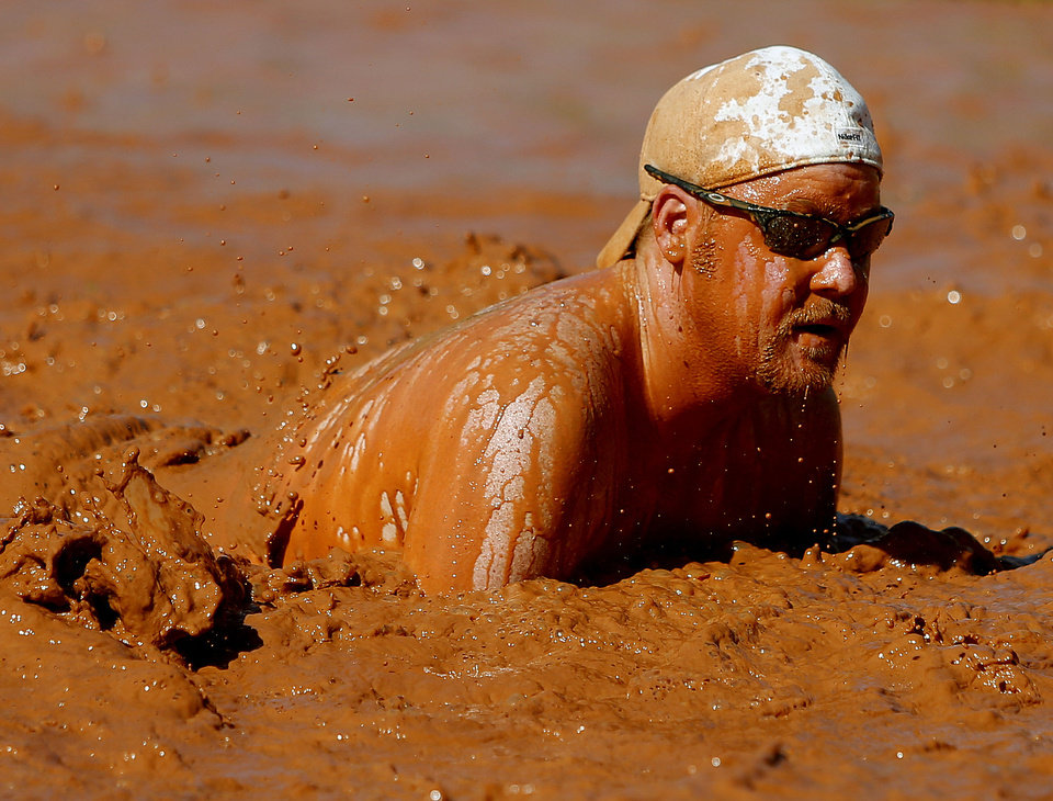 Photo - Jon Felmet gets up after falling in the mud during the MUDD Volleyball Tournament benefiting the Muscular  Dystrophy Association. Photo by Bryan Terry, The Oklahoman  BRYAN TERRY - THE OKLAHOMAN