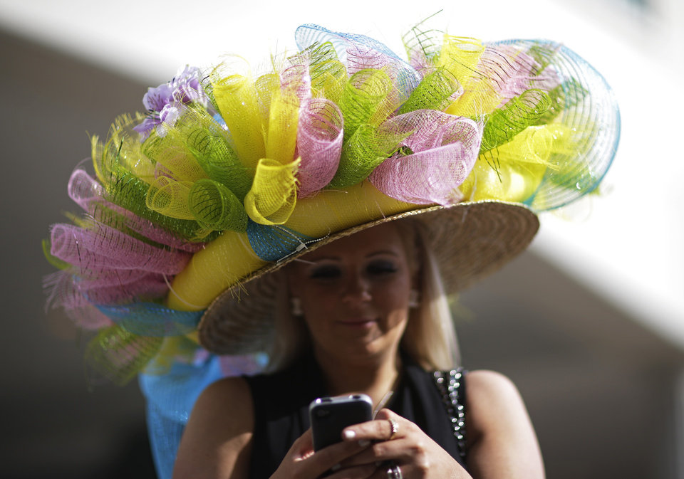 Ashley Cebak of Chicago looks at her phone before the 140th running of the Kentucky Derby horse race at Churchill Downs Saturday, May 3, 2014, in Louisville, Ky. (AP Photo/David Goldman)