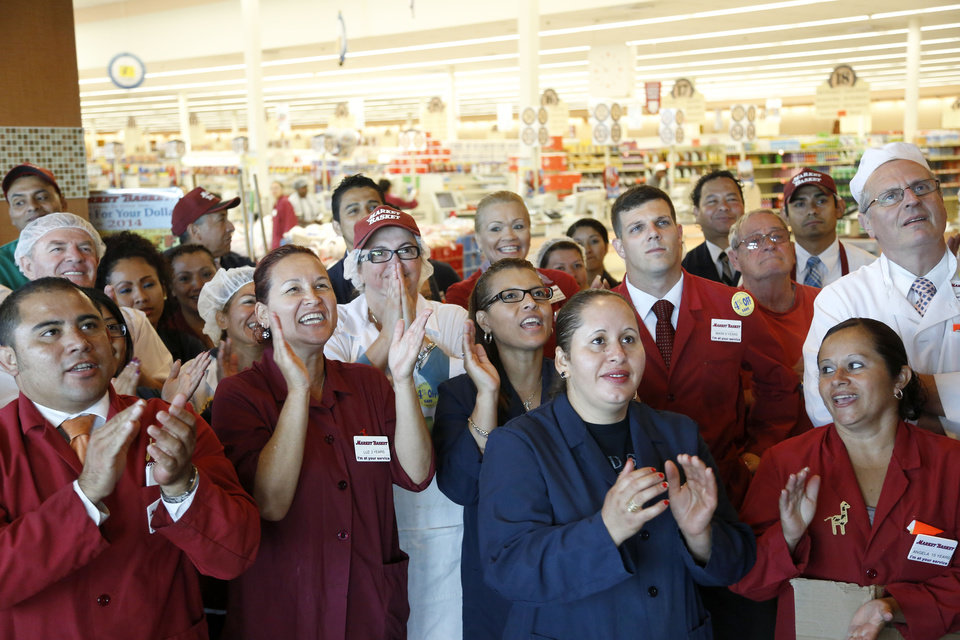 Photo - Market Basket employees clap and cheer while watching a televised speech by restored Market Basket CEO Arthur T. Demoulas, at a supermarket location, in Chelsea, Mass., Thursday, Aug. 28, 2014. A six-week standoff between thousands of employees of the New England supermarket chain and management has ended with the news that beloved former CEO Demoulas is back in control after buying the entire company. Demoulas made the speech to workers in Tewksbury, Mass. (AP Photo/Steven Senne)