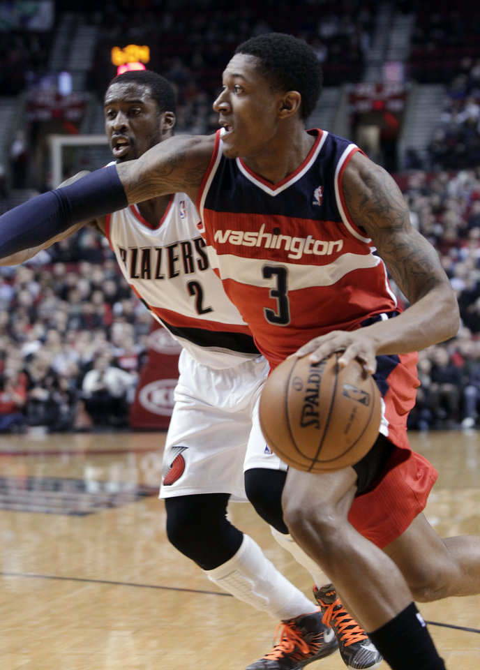 Photo - Washington Wizards guard Bradley Beal, right, drives past Portland Trail Blazers guard Wesley Matthews during the first quarter of an NBA basketball game in Portland, Ore., Monday, Jan. 21, 2013. (AP Photo/Don Ryan)