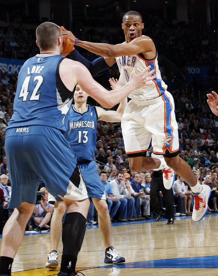 Photo - Oklahoma City's Russell Westbrook (0) passes the ball away from Kevin Love (42) and Luke Ridnour (13) of Minnesota during the NBA basketball game between the Minnesota Timberwolves and the Oklahoma City Thunder at the Oklahoma City Arena, Monday, November 22, 2010, in Oklahoma City. Photo by Nate Billings, The Oklahoman