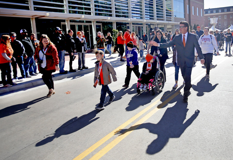 Photo - Oklahoma State head coach Mike Gundy waves to fans as he walks to the stadium during the college football game between the Oklahoma State University Cowboys and the TCU Horned Frogs at Boone Pickens Stadium in Stillwater, Okla.,  Saturday, Nov. 2, 2019. [Sarah Phipps/The Oklahoman]