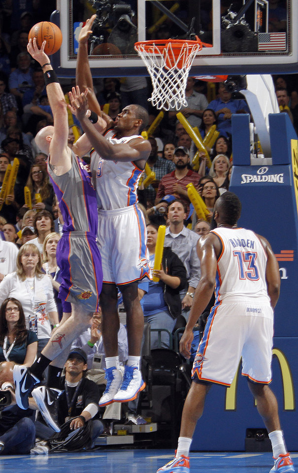 Photo - Oklahoma City Thunder power forward Serge Ibaka (9) blocks a shot by Phoenix Suns center Marcin Gortat (4) during the NBA basketball game between the Oklahoma City Thunder and the Phoenix Suns at the Chesapeake Energy Arena on Wednesday, March 7, 2012 in Oklahoma City, Okla.  Photo by Chris Landsberger, The Oklahoman