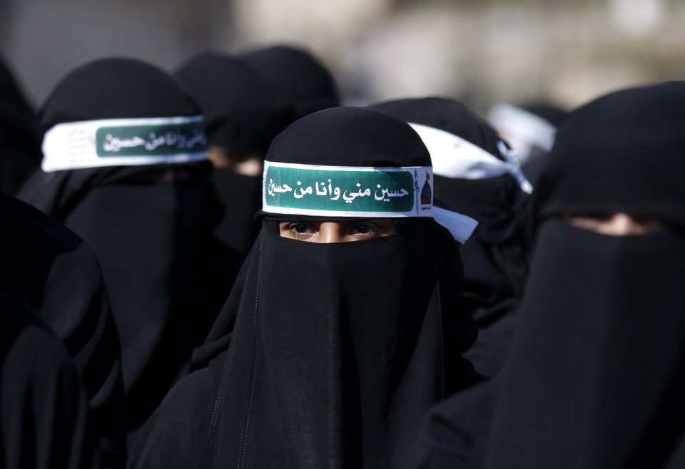A Yemeni Shiite woman, center, wearing a head band with Arabic reading,