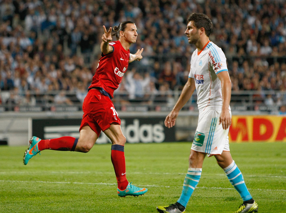 Photo -   Paris Saint Germain's Swedish forward Zlatan Ibrahimovic, left, reacts after scoring against Marseille, asMarseille's French forward Andre-Pierre Gignac looks on, during their League One soccer match, in Marseille, southern France, Sunday, Oct.7, 2012. (AP Photo/Claude Paris)