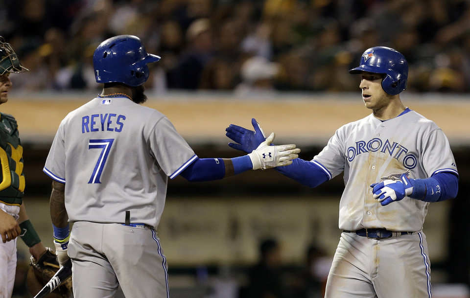 Photo - Toronto Blue Jays' Brett Lawrie, right, is congratulated by Jose Reyes, left, after Lawrie hit a home run off Oakland Athletics' A.J. Groiffin in the sixth inning of a baseball game Monday, July 29, 2013, in Oakland, Calif. (AP Photo/Ben Margot)