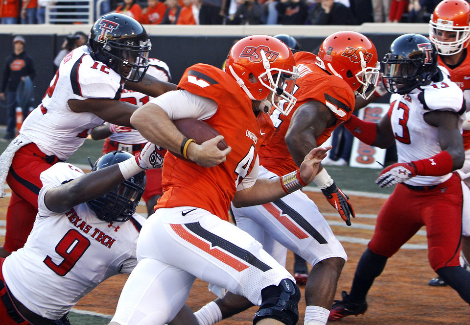 Oklahoma State quarterback J.W. Walsh (4) runs past Texas Tech linebacker Shawn Corker (9) for a touchdown in the second quarter of an NCAA college football game in Stillwater, Okla., Saturday, Nov. 17, 2012. (AP Photo/Sue Ogrocki)