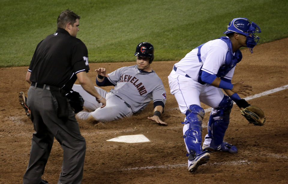 Photo - Cleveland Indians' Yan Gomes, center, beats the tag at home by Kansas City Royals catcher Salvador Perez, right, to score on a sacrifice fly hit by Jason Kipnis during the seventh inning of a baseball game on Friday, July 25, 2014, in Kansas City, Mo. (AP Photo/Charlie Riedel)
