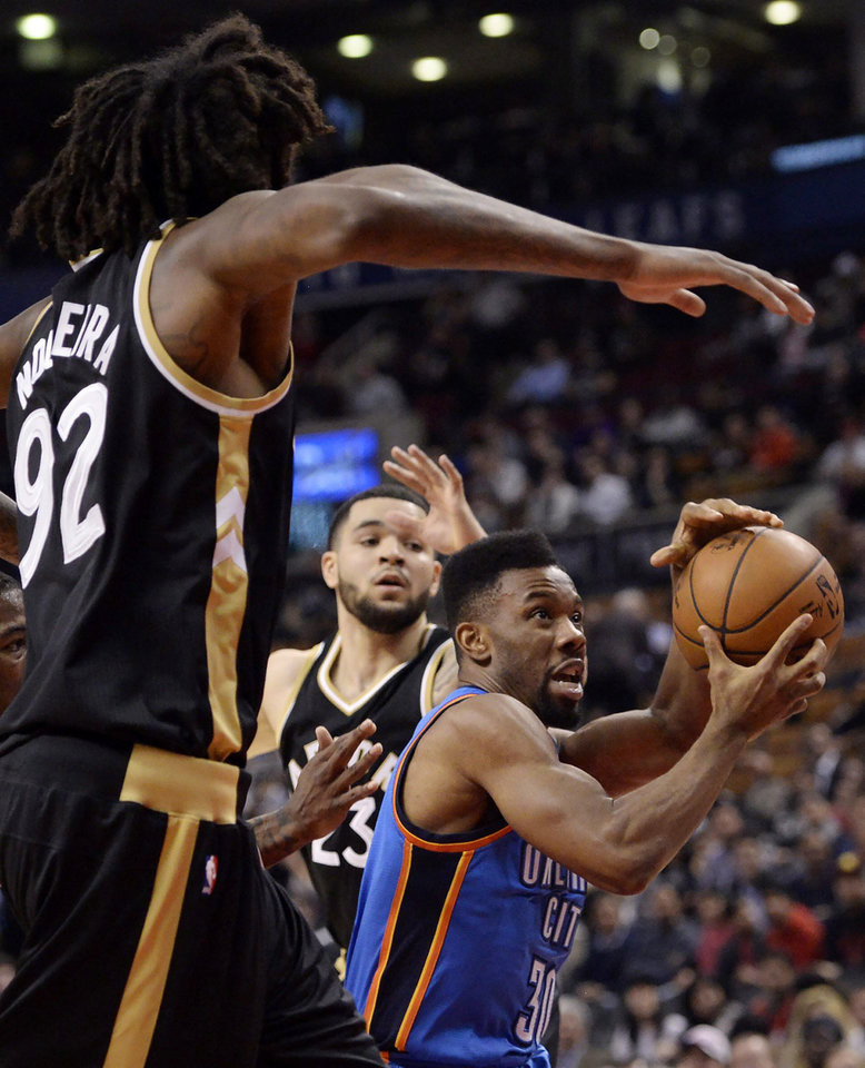 Photo -  Oklahoma City's Norris Cole, center, drives past Toronto's Luca Nogueira, left, and Fred VanVleet during Thursday night's NBA game at Air Canada Center. [PHOTO BY THE CANADIAN PRESS VIA AP]