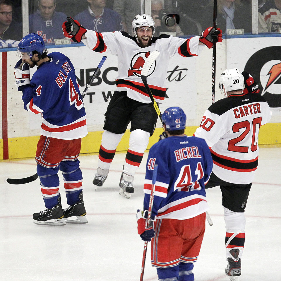 Photo -   New Jersey Devils' Stephen Gionta, top center, celebrates with Ryan Carter (20) after scoring a goal against the New York Rangers during the first period of Game 5 of an NHL hockey Stanley Cup Eastern Conference final playoff series, Wednesday, May 23, 2012, in New York. (AP Photo/Julio Cortez)