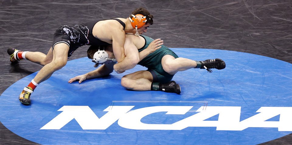 Photo - Oklahoma State's Tyler Caldwell, top, takes on Utah Valley's Curtis Cook in the 165 pound match during the 2014 NCAA Div. 1 Wrestling Championships at Chesapeake Energy Arena in Oklahoma City, Okla. on Thursday, March 20, 2014. Photo by Chris Landsberger, The Oklahoman