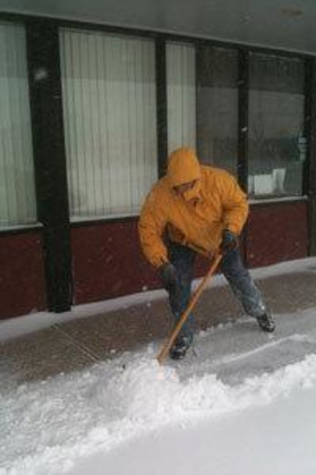 Photo - Dentist Steve Strange shovels snow in front of his business Broadway Family Dentistry in Edmond. Photo by Paul Hellstern
