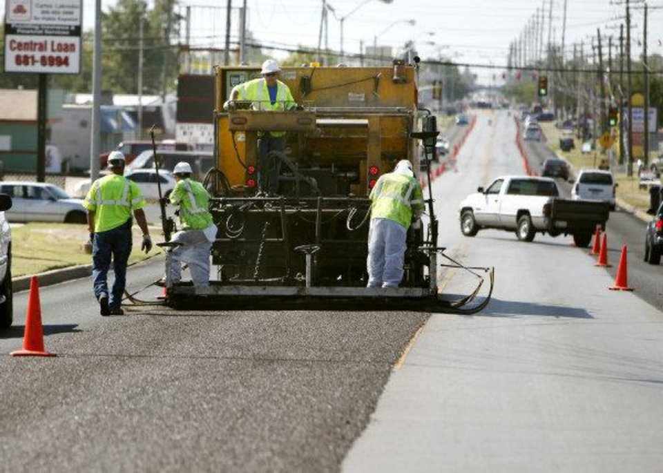 Crews do micro surfacing on S Pennsylvania Avenue between SW 44 and SW 59 in Oklahoma City on Friday. Micro surfacing extends the life of asphalt roadways and saves money. <strong>PAUL HELLSTERN - The Oklahoman</strong>