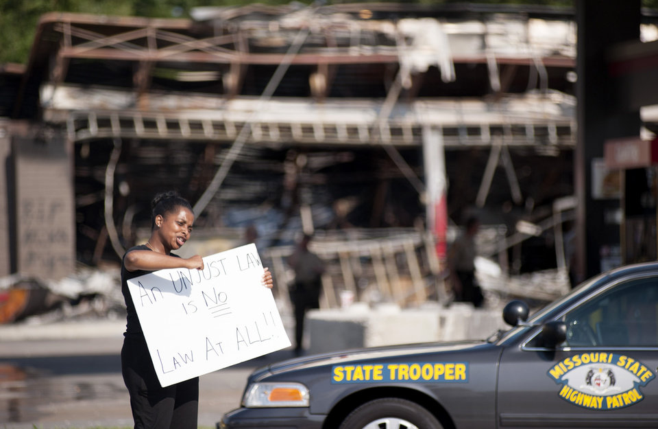 Photo - Protesters appeal to motorists for support while rallying on Monday, Aug. 11, 2014 in front of the QT gas station in Ferguson, Mo. that was looted and burned during rioting overnight that followed a candlelight vigil honoring 18-year-old Michael Brown, who was shot Aug. 9, 2014  by Ferguson police officers. Brown, who was killed in a confrontation with police in the St. Louis suburb, was shot Saturday and died following the confrontation with police. (AP Photo/Sid Hastings)