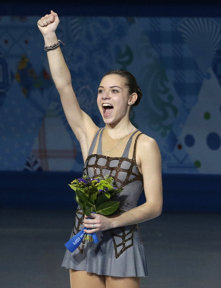Photo - Adelina Sotnikova of Russia celebrates on the podium as she celebrates placing first during the flower ceremony for the women's free skate figure skating final at the Iceberg Skating Palace during the 2014 Winter Olympics, Thursday, Feb. 20, 2014, in Sochi, Russia. (AP Photo/Darron Cummings)