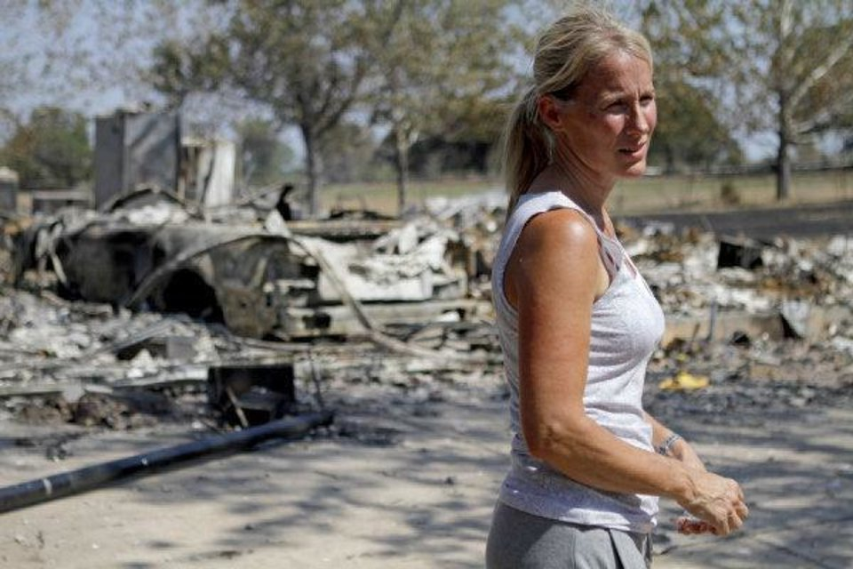 Photo - Steveanne Bielich stands by the remains of her home in northeast Oklahoma City, Wednesday, August 31, 2011. Bielich's home was destroyed by a wildfire on Tuesday, August 30, 2011. Photo by Bryan Terry, The Oklahoman ORG XMIT: KOD