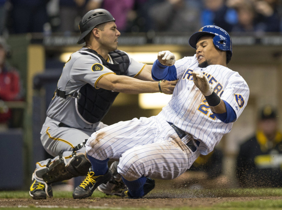 Photo - Milwaukee Brewers' Carlos Gomez, right, is tagged out at home by Pittsburgh Pirates' Tony Sanchez during the seventh inning of a baseball game on Sunday, April 13, 2014, in Milwaukee. (AP Photo/Tom Lynn)