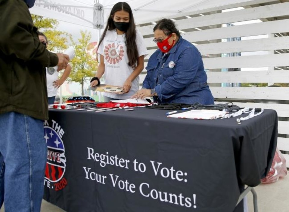 Photo -  Codie Topetchy, left, and Roxanna Foster, with Rock the Native Vote, help a man register to vote Tuesday. [Bryan Terry/The Oklahoman]