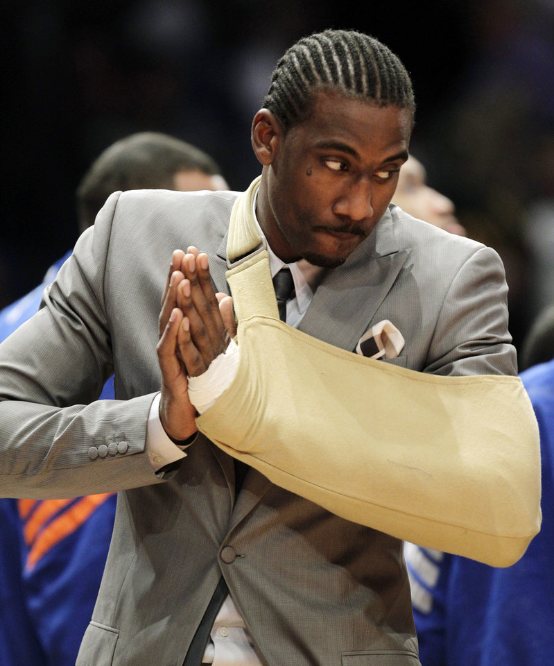 Photo -   New York Knicks forward Amare Stoudemire watches from the baseline with his arm in a sling before Game 3 of an NBA basketball first-round playoff series at Madison Square Garden in New York, Thursday, May 3, 2012. Stoudemire sat the game out after a surgeon repaired a muscle in his hand Tuesday after he cut it punching through the glass of a fire extinguisher case following Game 2. (AP Photo/Kathy Willens)