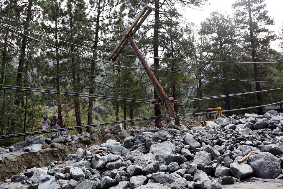 Photo - Rocks and mud have brought down a utility pole in the mountain community of Forest Falls in the San Bernardino Mountains Monday, Aug. 4, 2014. Crews cleared roads in an area where some 2,500 had been stranded after thunderstorms caused mountain mudslides in Southern California over the weekend, while authorities estimated that between six and eight homes were badly damaged and likely uninhabitable. One person was found dead in a vehicle that was caught in a flash flood. A group of campers spent the night at a community center near Forest Falls. (AP Photo/Nick Ut)