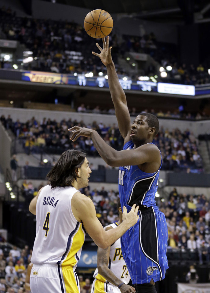 Photo - Orlando Magic forward Andrew Nicholson, right, shoots over Indiana Pacers forward Luis Scola in the first half of an NBA basketball game in Indianapolis, Monday, Feb. 3, 2014. (AP Photo/Michael Conroy)