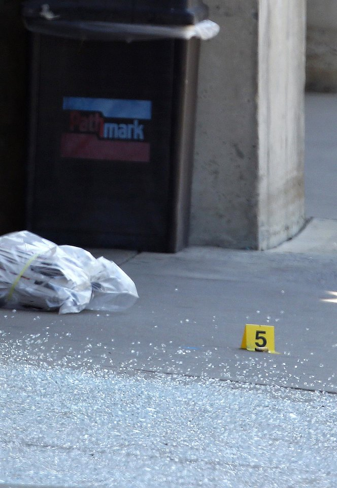 Photo -   An evidence marker stands next to broken glass in front of a Pathmark grocery store where three people died in an early morning shooting in Old Bridge, N.J., Friday, Aug. 31, 2012. Officials say a supermarket employee killed two people at the store early Friday and then fatally shot himself. Authorities say he opened fire on employees he saw when he walked into the Pathmark store. The store's front windows were shattered by gunfire. The motive is being investigated.(AP Photo/Julio Cortez)