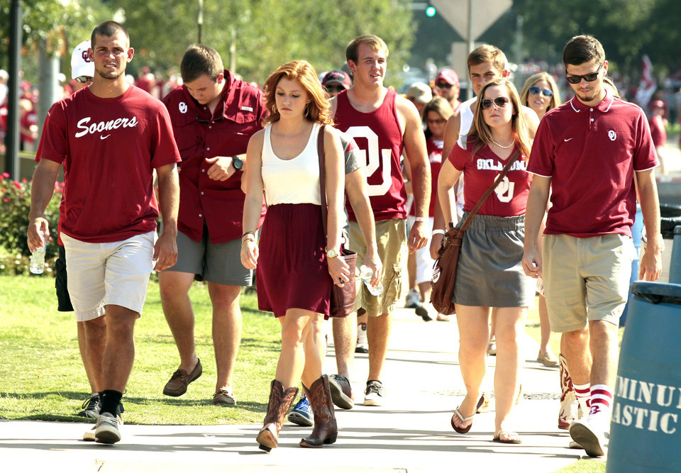 Photo - Fans walk slowly in the over 100 degree  heat before the college football game where the University of Oklahoma Sooners (OU) play the University of Louisiana Monroe Warhawks at Gaylord Family-Oklahoma Memorial Stadium in Norman, Okla., on Saturday, Aug. 31, 2013. Photo by Steve Sisney, The Oklahoman