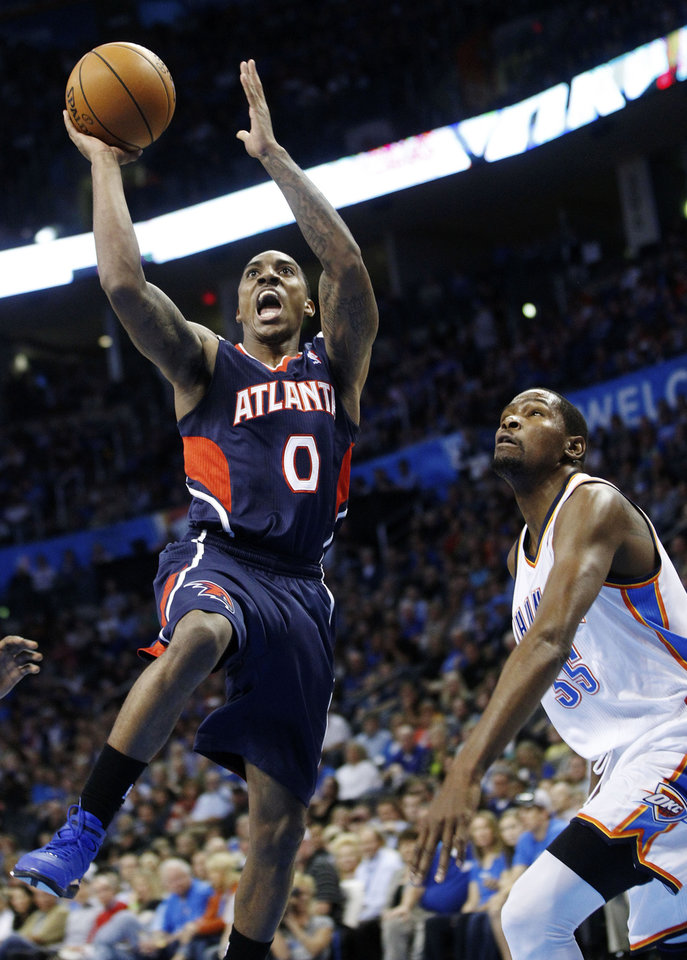 Atlanta Hawks guard Jeff Teague (0) shoots in front of Oklahoma City Thunder forward Kevin Durant (35) during the first quarter of an NBA basketball game in Oklahoma City, Sunday, Nov. 4, 2012. (AP Photo/Sue Ogrocki)