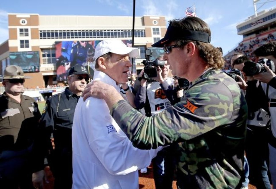 Photo -  Kansas coach Les Miles, left, greets the man who replaced him as Oklahoma State's head coach, Mike Gundy, after the Cowboys beat the Jayhawks 31-13 Saturday in Stillwater. [Sarah Phipps/The Oklahoman]