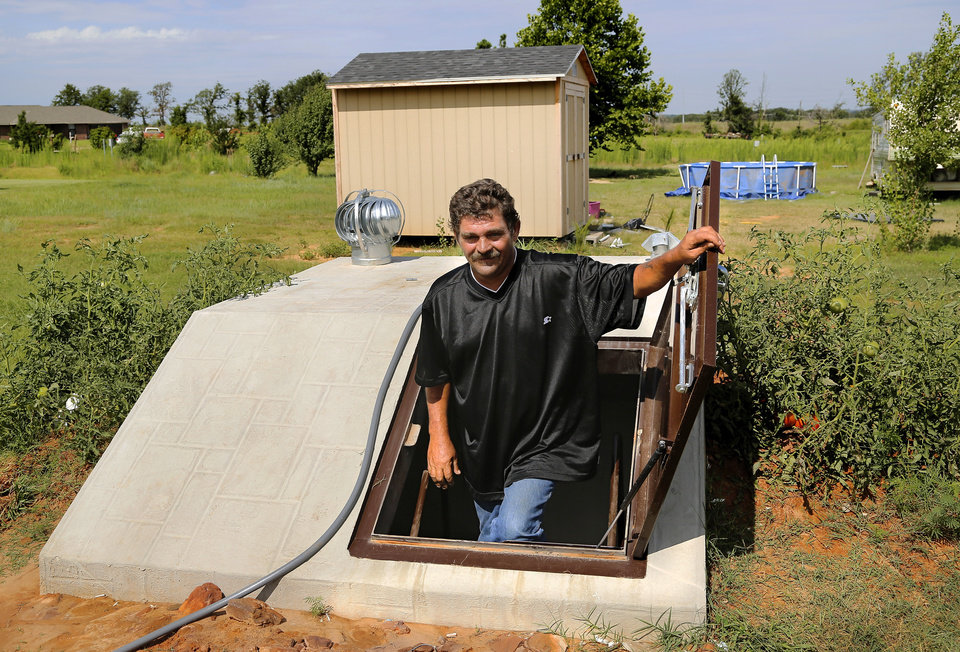 Photo -  Clayton Cook shows his new storm cellar on the property where his mobile home sits in Steelman Estates.     Jim Beckel -  THE OKLAHOMAN