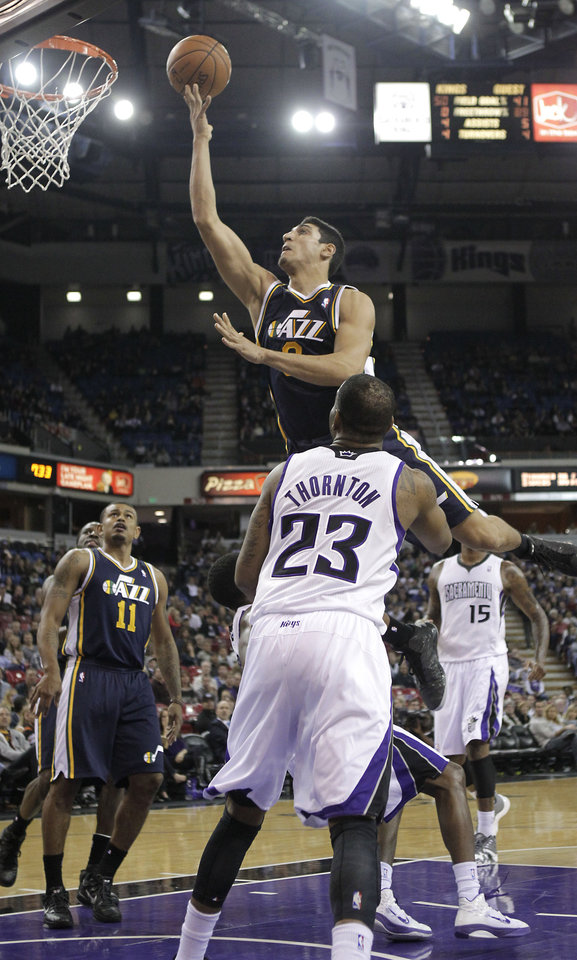 Photo -   Utah Jazz center Enes Kanter, of Turkey, center, goes to the basket over Sacramento Kings guard Marcus Thornton during the first half of an NBA basketball game in Sacramento, Calif., Saturday, Nov. 24, 2012. (AP Photo/Rich Pedroncelli)
