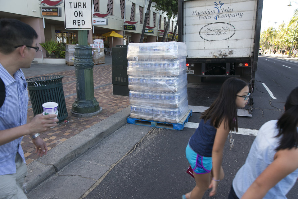 Photo - People walk past a pallet of bottled water being delivered to a shop in Waikiki in Honolulu on Thursday, Aug. 7, 2014. With Iselle, Hawaii is expected to take its first direct hurricane hit in 22 years. Tracking close behind it is Hurricane Julio. (AP Photo/Marco Garcia)