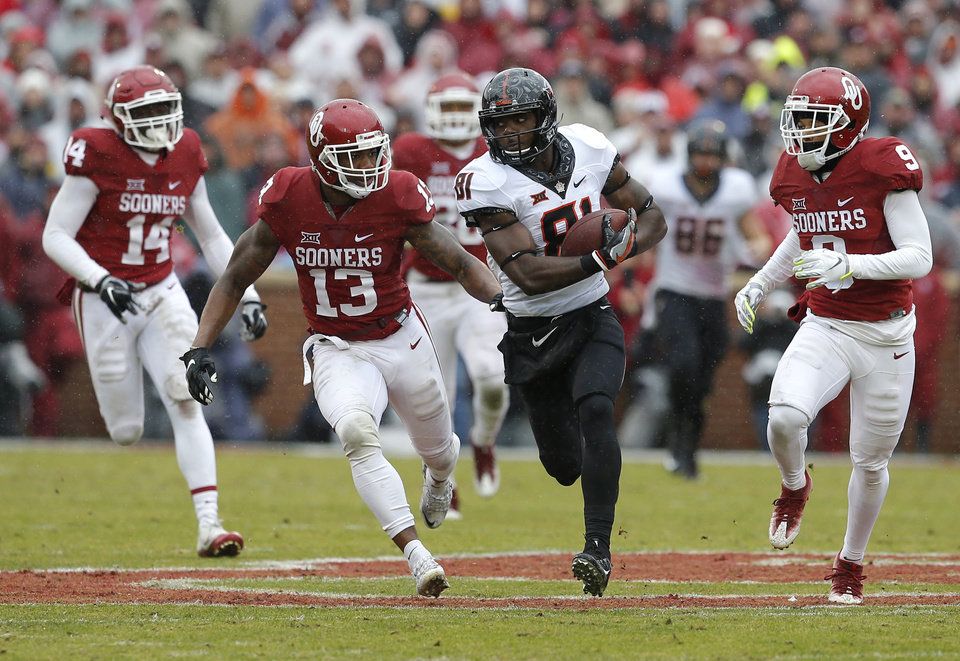 Photo - Oklahoma State's Jhajuan Seales (81) runs past Oklahoma's Ahmad Thomas (13) and Jordan Parker (9) during the Bedlam college football game between the Oklahoma Sooners (OU) and the Oklahoma State Cowboys (OSU) at Gaylord Family - Oklahoma Memorial Stadium in Norman, Okla., Saturday, Dec. 3, 2016. Oklahoma won 38-20. Photo by Bryan Terry, The Oklahoman