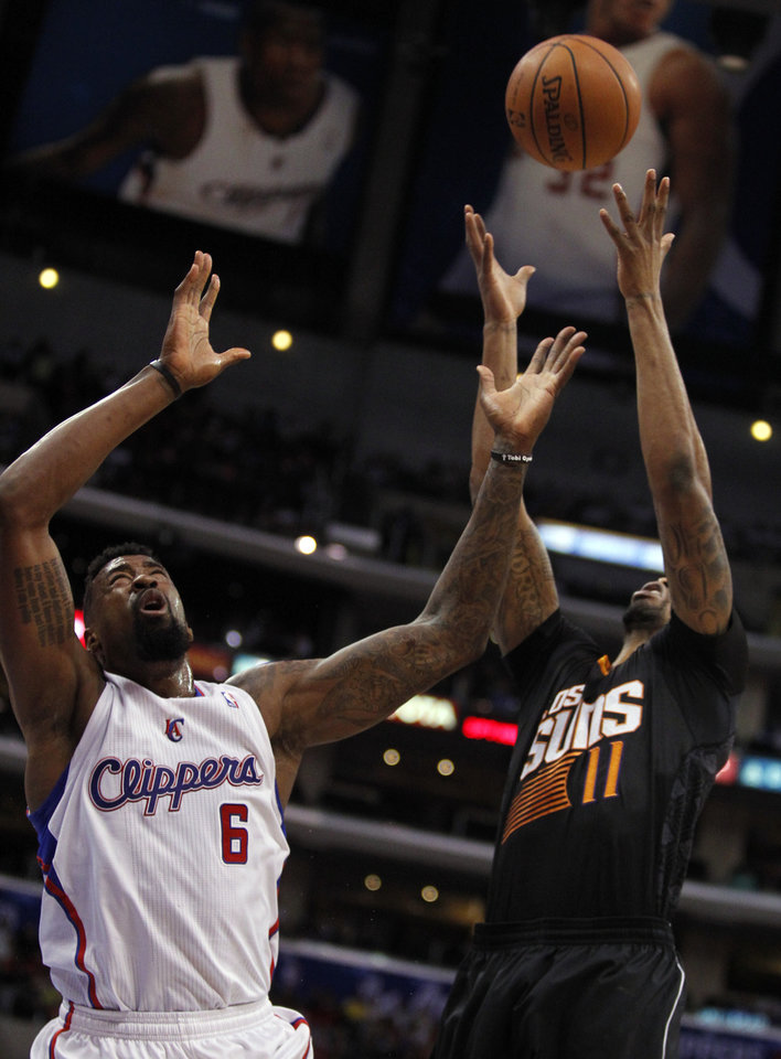 Photo - Los Angeles Clippers center DeAndre Jordan (6) battles for a rebound against Phoenix Suns forward Markieff Morris (11) during the first half of an NBA basketball game Monday, March 10, 2014, in Los Angeles. (AP Photo/Alex Gallardo)